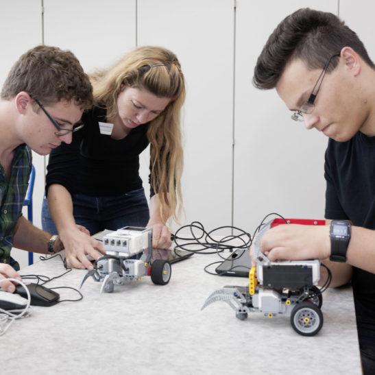 Drei Personen, die einen Roboter programmieren